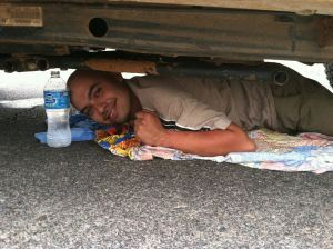 Activist Raul Alcaraz Ochoa beneath a Border Patrol vehicle.